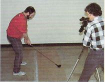 Bruce Carver films Roger taking a golf swing.
