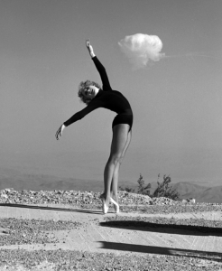 "Showgirl Sally McCloskey does an ""atomic ballet"" in front of a shot."