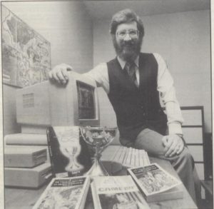 John Sweeney with his freshly won Holy Grail and the things he had to use to win it: his computer, his Lancelot game, and lots and lots of reference books.