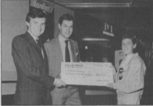 Matthew Woodley, at right, gets his check for being the first to solve Eureka!.